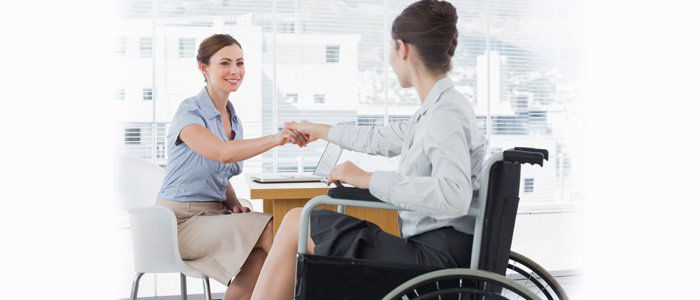 Woman sitting at a desk shaking hands with woman in wheelchair. Visit Choosework.ssa.gov