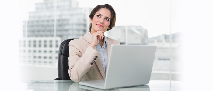 Woman sitting at desk in front of computer, thinking